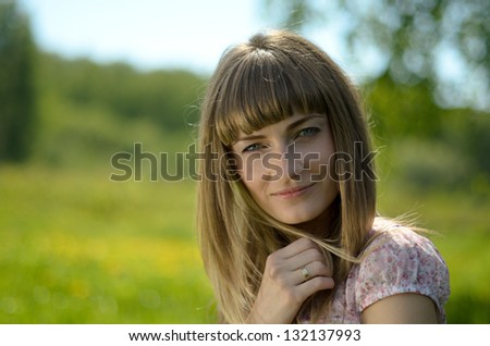 Beautiful young woman portrait in a green park