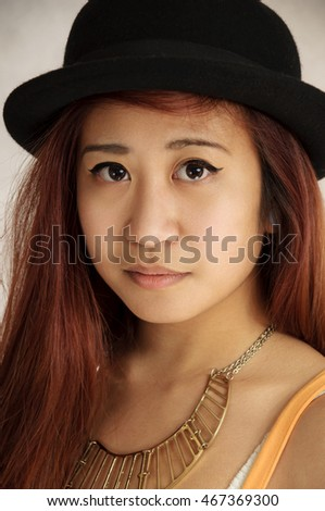 Beautiful young woman. Portrait of asian woman. Gray background girl with a black hat.