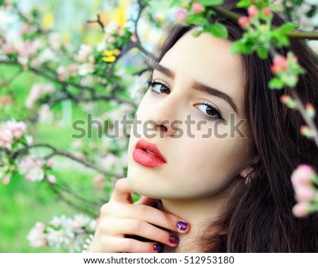 Beautiful young woman. Portrait of girl, standing near the blooming tree