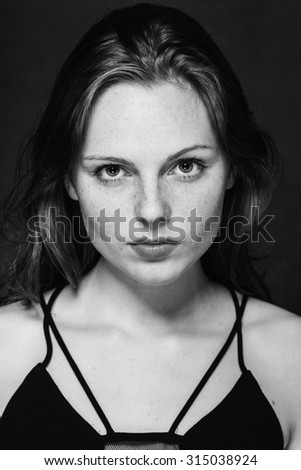 Beautiful young woman portrait on black background studio with freckles black and white - stock photo