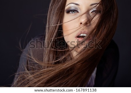 beautiful young woman portrait with long hair in motion, studio shot - stock photo