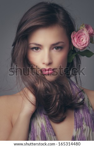 beautiful young  woman portrait with roses in hair looking at camera studio shot - stock photo
