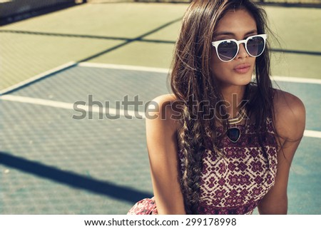 beautiful young woman posing at tennis court in fashion clothes and jewelry among palm trees. Fashion photo with sunglasses