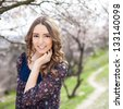 Beautiful young woman posing in a flowering spring park - stock photo