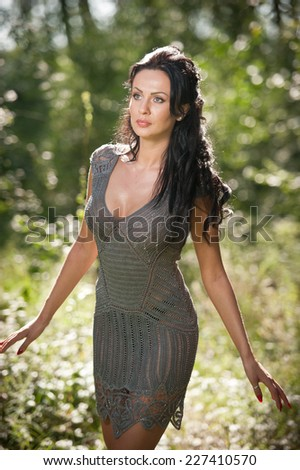Beautiful young woman posing in a summer meadow. Portrait of attractive brunette girl with long hair relaxing in nature, outdoor shot in sunny day. Lady in gray enjoying the nature, harmony concept - stock photo