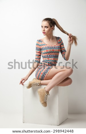 Beautiful young woman posing in dress on cube at studio - stock photo