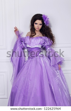 Beautiful young woman posing in elegant dress - stock photo
