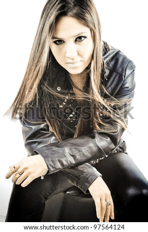 Beautiful young woman posing in studio, wearing black leather clothes, with rock attitude, on white background.