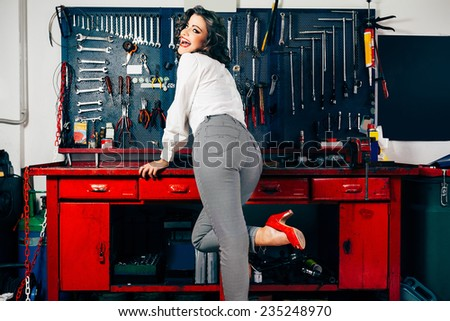 Beautiful young woman posing in vintage car repair shop - stock photo