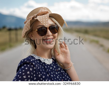 Beautiful young woman posing on a road in mountains - stock photo