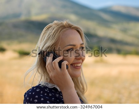 Beautiful young woman posing on a road in mountains with cellpho - stock photo