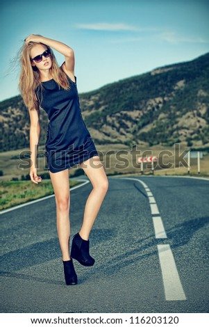 Beautiful young woman posing on a road over picturesque landscape. - stock photo