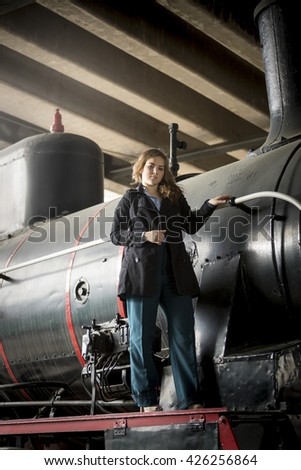 Beautiful young woman posing on old steam locomotive - stock photo