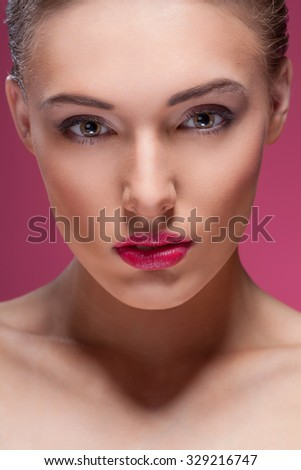 Beautiful young woman posing over pink background