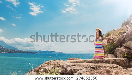Beautiful young woman posing over sea and mountains. Summer travel day.  Copay space - copyspace - stock photo