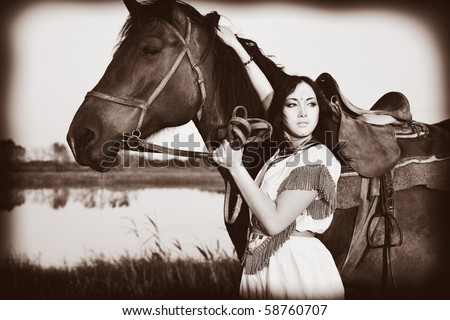 Beautiful young woman posing with a brown horse. - stock photo