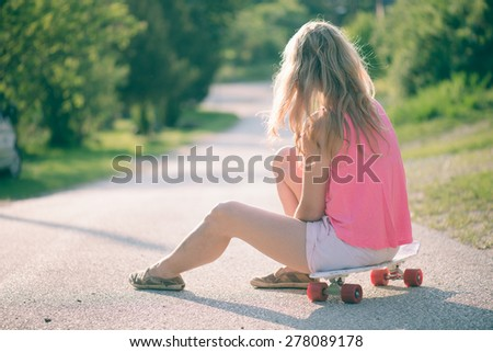 Beautiful young woman posing with a skateboard - stock photo