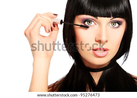 Beautiful young woman posing with mascara. Isolated over white. - stock photo