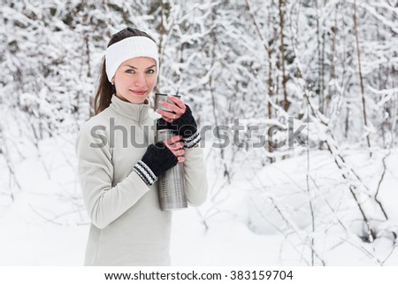 Beautiful Young Woman pours and drinks tea from a thermos after jogging in the winter forest. Trees in the snow. Weather snow cloud. Fitness on the street in the winter. - stock photo