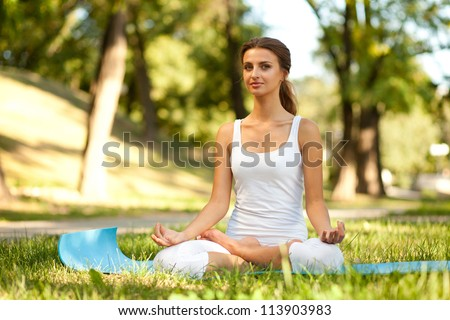 Beautiful young woman practices yoga in nature. Lotus Pose, eyes opened