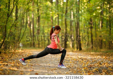 Beautiful young woman practicing or exercising, doing sports in park