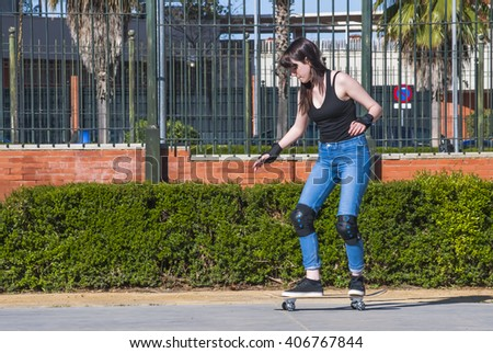 Beautiful young woman practicing with the skateboard on the street on a sunny day