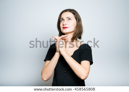 beautiful young woman praying, studio photo isolated on a gray background - stock photo