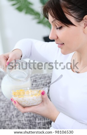Beautiful young woman preparing breakfast in the morning - stock photo