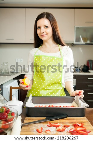 Beautiful young woman preparing strawberry cake