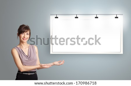Beautiful young woman presenting modern copy space - stock photo