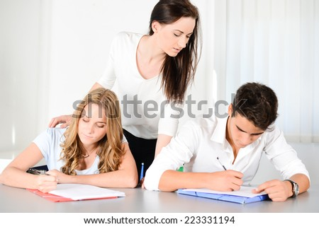 beautiful young woman private teacher helping two students doing their homework