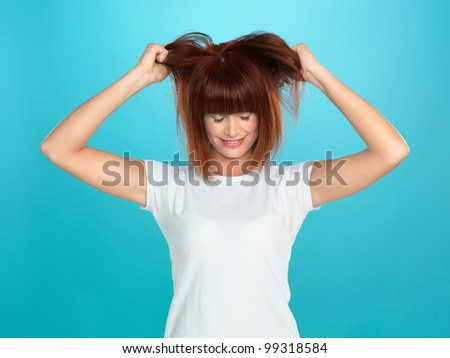 beautiful, young woman pulling her hair, on blue background