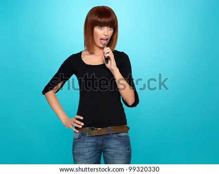 beautiful, young woman pulling her tongue with a pliers, on blue background