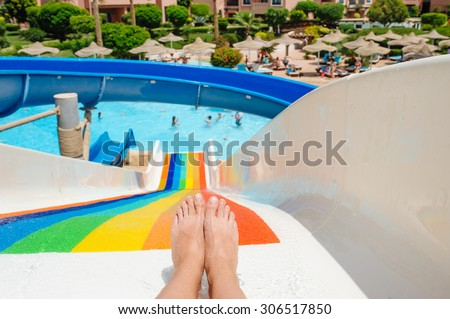 beautiful young woman pulls off the slides in the water park - stock photo
