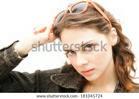Beautiful young woman puts on sunglasses, isolated on white background