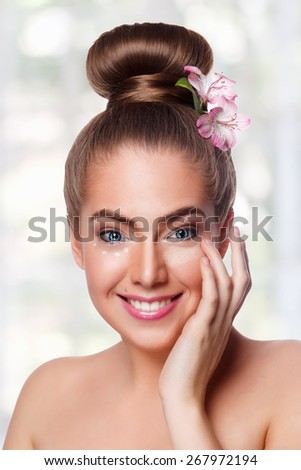 Beautiful young woman putting cream under eyes - stock photo