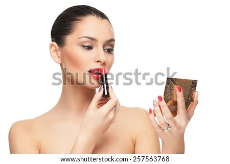 Beautiful young woman putting lipstick on lips - stock photo