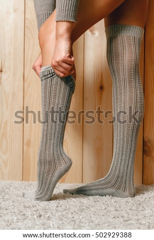 Beautiful young woman putting on stockings, standing on the carpet