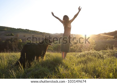 Beautiful young woman raises her arms to the sun whilst walking her dog - stock photo