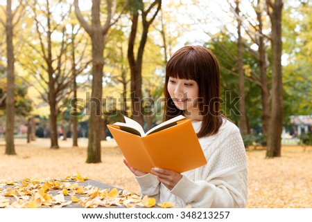 Beautiful young woman reading a book  in autumn