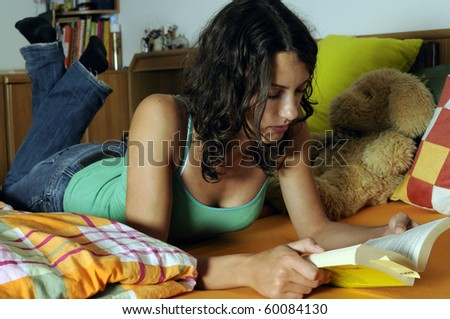 Beautiful young woman reading a book in her bed. - stock photo