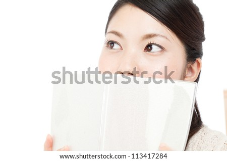 Beautiful young woman reading a book. Portrait of asian.