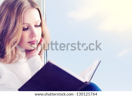 beautiful young woman reading a book while sitting at a window in the sky