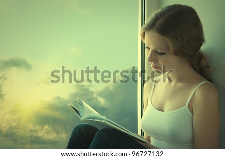beautiful young woman reading a book while sitting at a window in the sky and sunset - stock photo