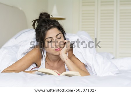 beautiful young woman reading book in the bed