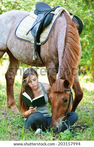 Beautiful young woman reading book with horse, against green of summer park. - stock photo