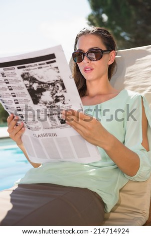 Beautiful young woman reading newspaper on sun lounger by swimming pool - stock photo