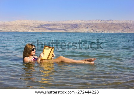 beautiful young woman reads a book floating in the waters of the Dead Sea in Israel - stock photo