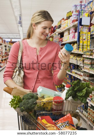 Beautiful young woman reads the label on a jar while shopping at a grocery store.  Vertical shot.