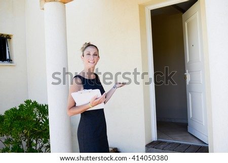beautiful young woman real estate agent in front of a house for sale - stock photo